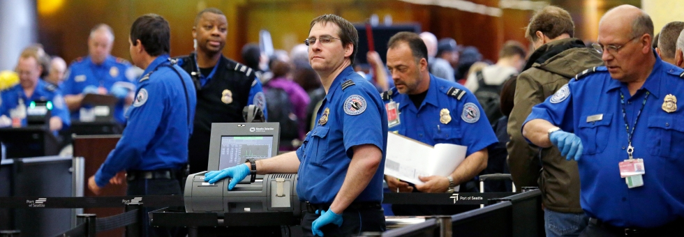 In this photo taken Tuesday, March 24, 2015, TSA agents work at a security check-point at Seattle-Tacoma International Airport in SeaTac, Wash. (AP Photo/Elaine Thompson)